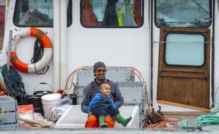 Un pêcheur mi'kmaq serre son fils sur son bateau avant de partir poser des pièges à Saulnierville, en Nouvelle-Écosse, le 21 octobre 2020.